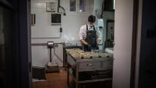 A cook works in Barcelona, Spain on April 16, after his restaurant's kitchen has been converted to prepare food for healthcare professionals and vulnerable people.