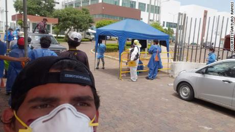 Arturo Ramos, 24, on day 3 of looking through the bodies in the hospital morgue and containers for his father. On the right, vehicles in line with the coffins waiting to collect the remains of their loved ones.