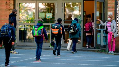 The children respect the rules of social removal when they enter Petri elementary school in Dortmund, western Germany, on Thursday, while the school reopens for some pupils.