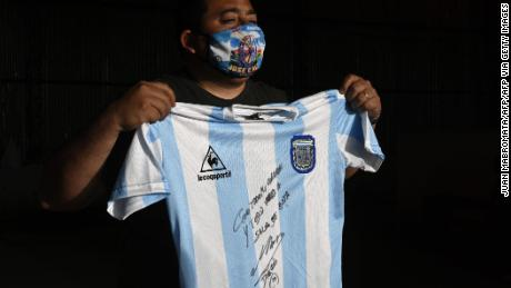 A man holds a replica of the shirt of the Argentine soccer team used during the 1986 World Cup final and signed by Diego Maradona.