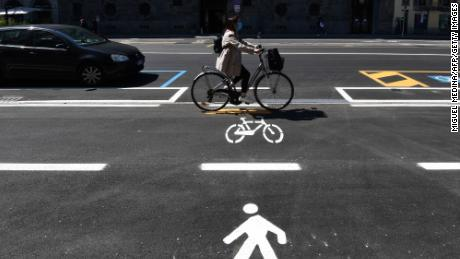 A woman goes along a cycle path in Milan.