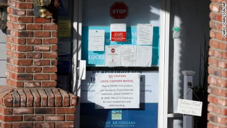 Warning notices have been posted on a door at the entrance to the Cedar Mountain Post Acute nursing facility in Yucaipa, California. There have been 21 resident deaths - the largest number of Covid-19 deaths in any facility in San Bernardino County.