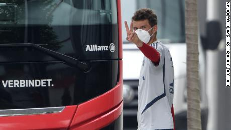 Bayern Munich forward Thomas Mueller wears a mask while leaving a training session.