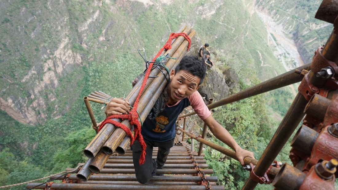 A man climbs up the mountain to Atule'er village in Sichuan province, China.