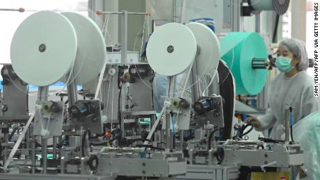 A staff of Taiwans Universal Incorporation, one of the major mask manufacturers, operates machinery in a factory in Tainan, southern Taiwan.