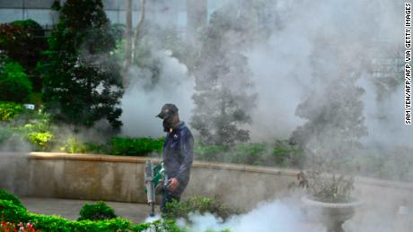 A masked worker disinfects a park to prevent the spread of coronavirus in the new city of Taipei on March 9.
