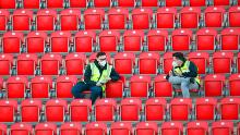The stewards wearing protective masks sit in the empty stands of the Union Berlin home stadium, with all the Bundesliga games until the end of the season taking place behind closed doors.