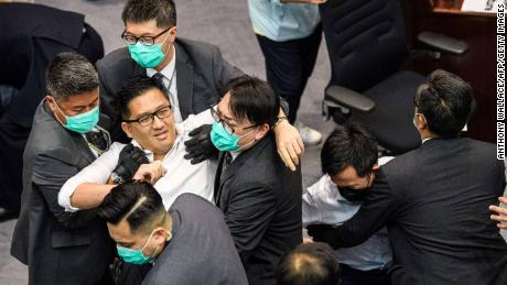 Lam Cheuk-ting is removed by security personnel following the fight.