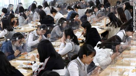 Students have lunch at tables equipped with plastic barriers to prevent the possible spread of the new coronavirus in the cafeteria of the Jeonmin High School in Daejeon, South Korea, Wednesday 20 May.