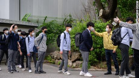 Students wearing masks do a temperature check when they arrive at Keongbok High School in Seoul on May 20, 2020.