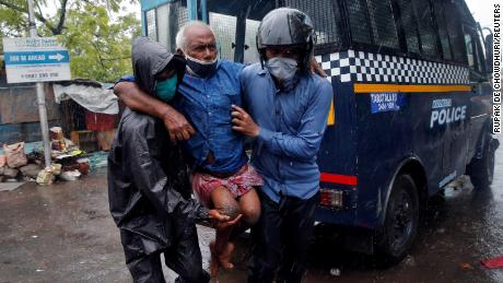 Police officers transport a disabled man to a safer place following his evacuation from a slum in Calcutta, India.