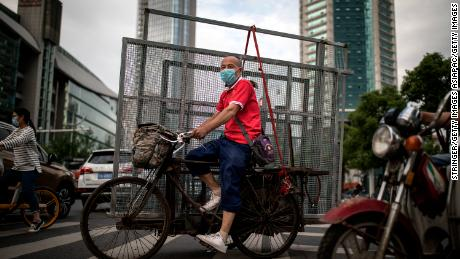 A man wearing a face mask drives the tricycles to transport iron nets to Wuhan on May 11th.