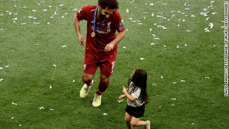 Salah celebrates with her daughter Makka after her team won during the UEFA Champions League final.