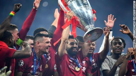 Salah lifts the Champions League trophy.