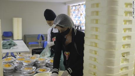 Volunteers prepare some of the 10,000 meals that are delivered to residents of the Paraisopolis favela every day, so they don't need to leave their homes to eat.