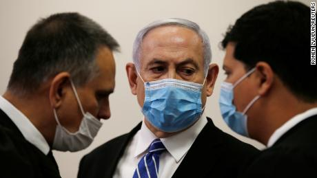 Prime Minister Benjamin Netanyahu stays with lawyers at the Jerusalem District Court on Sunday.