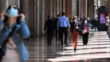 People walk through a commercial colonnade in Milan on May 18.