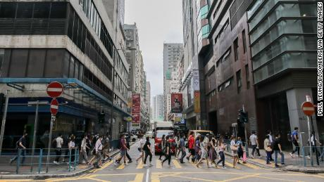 Pedestrians wearing protective masks cross a road during the morning rush hour in the Kwun Tong district of Hong Kong on May 6.