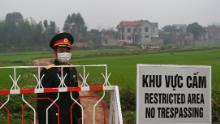 An army officer of a Vietnamese people stands next to a sign warning of the blockade in the city of Son Loi in the province of Vinh Phuc on February 20.
