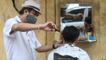 A roadside barber wearing a face mask makes a haircut to a client in Hanoi.