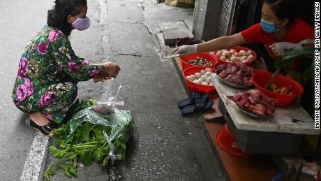 A woman practices social removal while shopping from behind a line in a wet market in Hanoi.