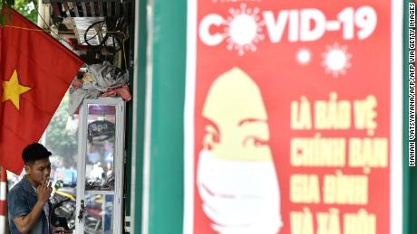 A propaganda poster about preventing the spread of coronavirus is seen on a wall while a man smokes a cigarette on a Hanoi street.