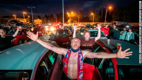 Fans rejoice as they watch the Czech First Division football game between FC Viktoria Plzen and AC Sparta Praha in a drive-in cinema in Plzen, Czech Republic.