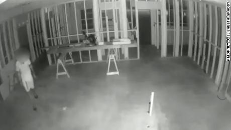 The night video shows a man walking around the house under construction.