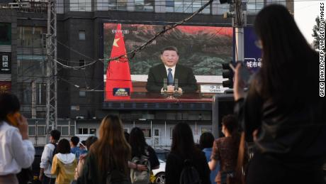 A news program shows Chinese President Xi Jinping speaking via video link to the World Health Assembly on a giant screen next to a Beijing street on May 18.