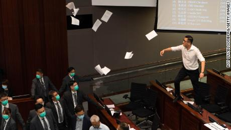 Lam Cheuk-ting, a pro-democracy lawmaker, on the right, throws documents into the air in protest as security agents watch.