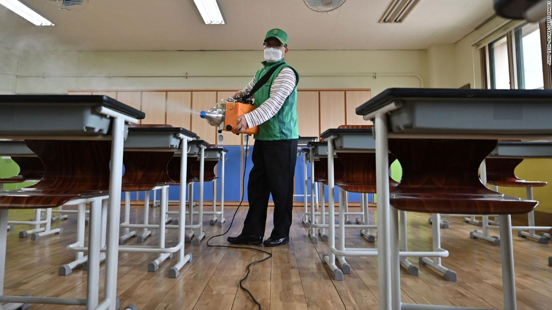 A worker sprays disinfectant in a classroom at a high school in Seoul earlier this month. South Korea has been held up as a global model in how to curb the coronavirus.
