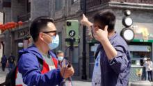 People wearing masks livestream on Qianmen Street on April 25 in Beijing, China.