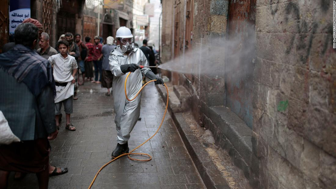 A health worker wearing a protective suit sprays disinfectant at a market in the old city of Sanaa in April.