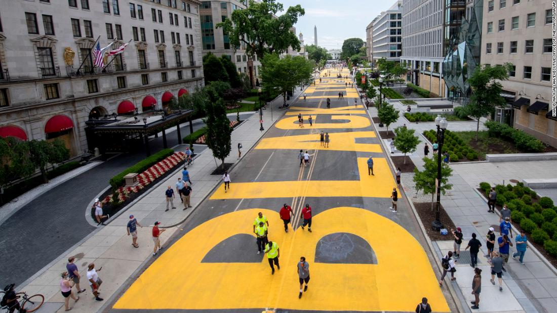 The words Black Lives Matter is painted in bright yellow letters on the road to the White House.