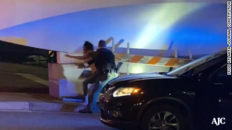 The video shows a woman being hit by an Atlanta policeman while being handcuffed