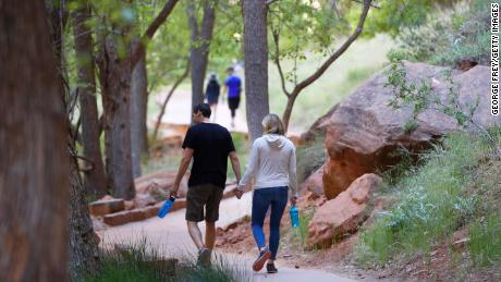 Hikers walking along a paved trail in Utah's Zion National Park, Utah, which had been closed due to the pandemic.
