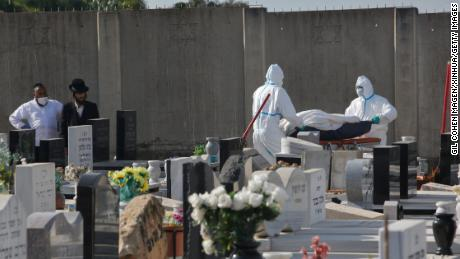 Funeral workers carry the body of a Covid-19 patient at a cemetery in the central Israeli city of Rehovot on April 21.