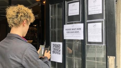 Plastic screens, tracings apps and table service. English pubs reopen on bittersweet day