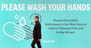 A man wearing a face mask walks past a sign urging people to wash their hands in Melbourne, Australia.