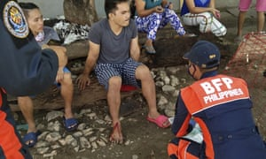 An injured man is treated after a strong earthquake struck in central Philippines.