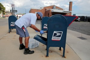FILE PHOTO: FILE PHOTO: A United States Postal Service (USPS) worker handles the mail in a drop-off box behind a post office in Oak Park, Michigan, U.S. August 17, 2020. REUTERS/Rebecca Cook/File Photo/File Photo