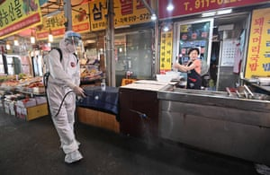 A health official wearing protective gear sprays disinfectant at a market near the Sarang Jeil Church in Seoul.