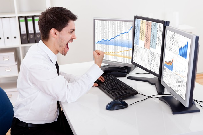 A stock investor pumping his fist as he looks at rising charts on his computer screens.
