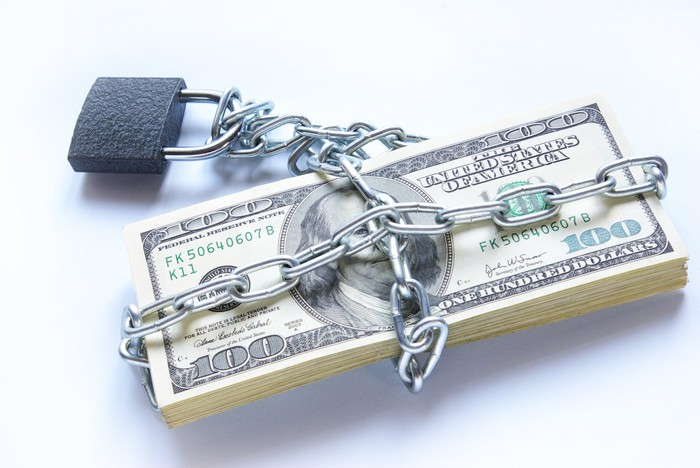 A neat stack of one hundred dollar bills chained up and locked.