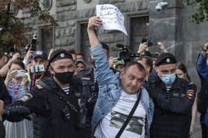 Police officers detain a protester as he comes to support Russian opposition leader Alexei Navalny in front of the building of the Federal Security Service on 20 August