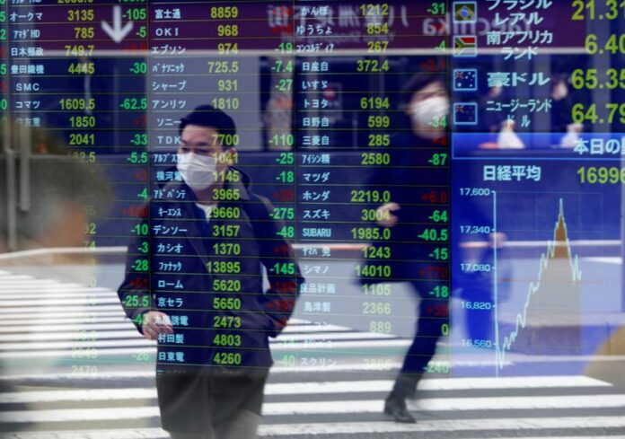 © Reuters. FILE PHOTO: Passersby wearing protective face masks are reflected on a screen displaying stock prices outside a brokerage in Tokyo