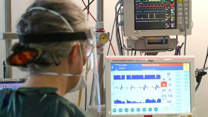 An ICU nurse monitors a ventilator at Frimley Park Hospital in Surrey