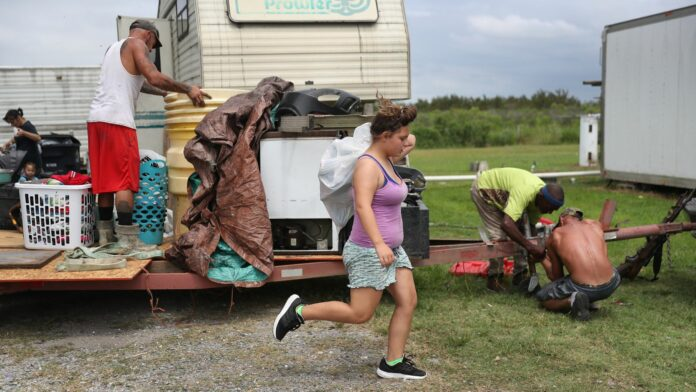 A family takes belongings from their home as the evacuate ahead of Hurricane Laura making landfall