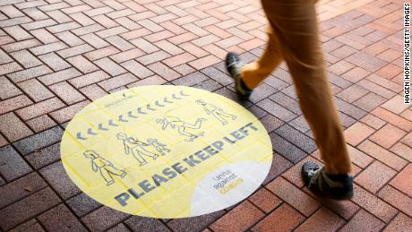 A pedestrian walks past a social distancing sign on August 14, 2020 in Wellington, New Zealand.