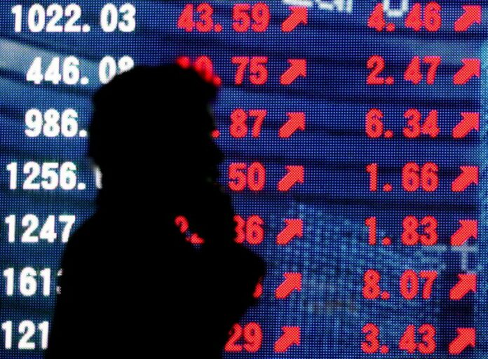 © Reuters. FILE PHOTO: Man is silhouetted against stock quotation board in Tokyo